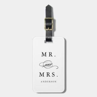 Sr. y señora en etiqueta del equipaje del blanco