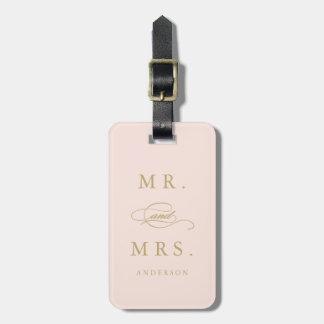 Sr. y señora en rosa y etiqueta del equipaje del