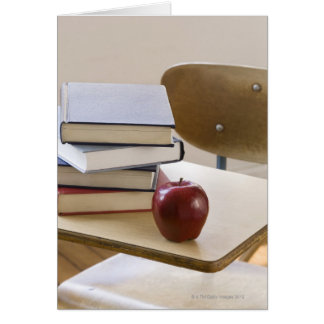 Stack of books, apple, and school desk card