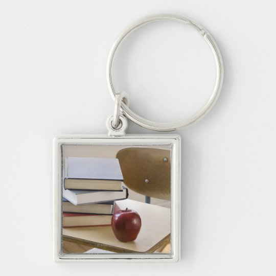 Stack of books, apple, and school desk keychain