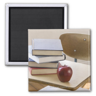 Stack of books, apple, and school desk magnet