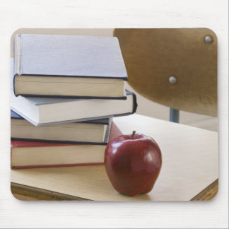 Stack of books, apple, and school desk mouse pad