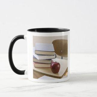 Stack of books, apple, and school desk mug