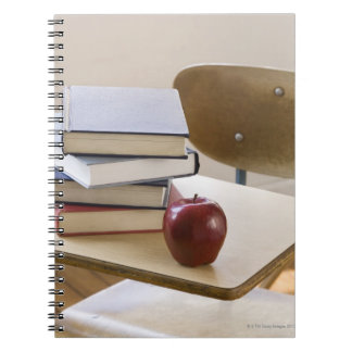 Stack of books, apple, and school desk spiral note book