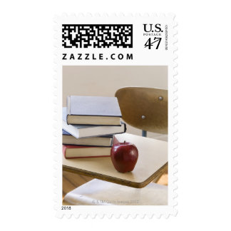Stack of books, apple, and school desk postage
