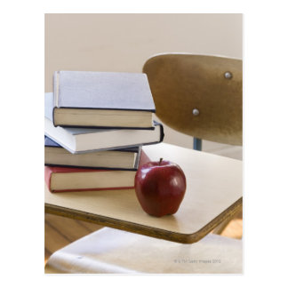 Stack of books, apple, and school desk postcard