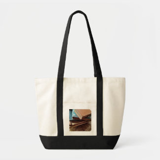 stack of books on old chair impulse tote bag