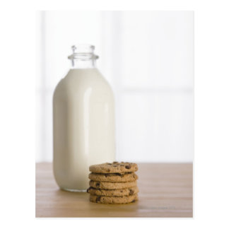 Stack of chocolate chip cookies milk in a glass postcard