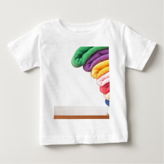 Stack of colorful microfiber towels toppling shirt
