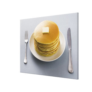 Stack of pancakes with butter on a plate canvas print