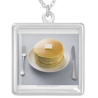 Stack of pancakes with butter on a plate silver plated necklace