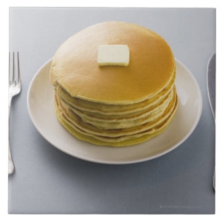 Stack of pancakes with butter on a plate tile