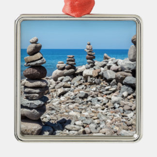 Stacked beach stones at blue sea metal ornament