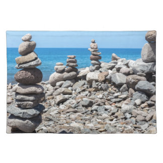 Stacked beach stones at blue sea placemat