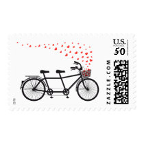 Stamp with tandem bicycle and flying red hearts