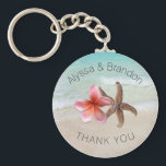 """Starfish Plumeria By the Sea Custom Wedding Favor Keychain<br><div class=""""desc"""">Beach wedding favor key ring with custom text.  A starfish and pink plumeria (frangipani) flower represent the couple.  The background is a tropical beach scene with pretty blue ocean water and beach sand.</div>"""