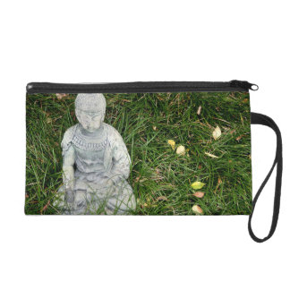 statue on leaf covered lawn wristlet clutch