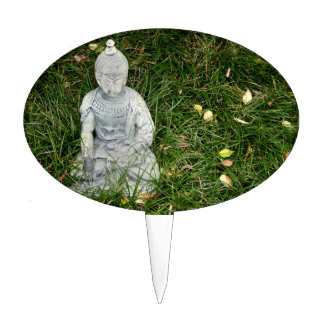 statue on leaf covered lawn cake topper