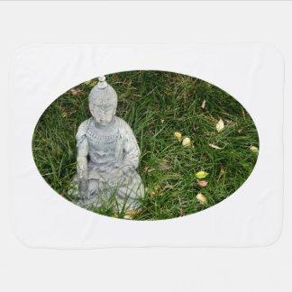 statue on leaf covered lawn stroller blanket