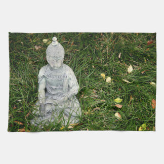 statue on leaf covered lawn towels