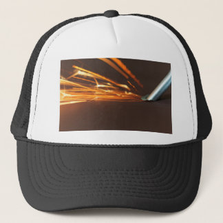 Steel tool on a grinder with sparks trucker hat