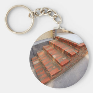 Steps of the porch outside the house under constru basic round button keychain