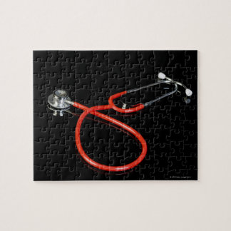 Stethoscope with its reflection on a black jigsaw puzzle