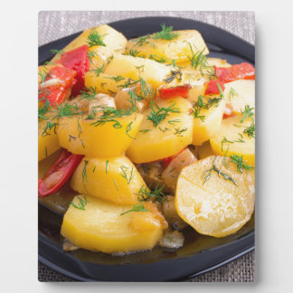 Stew of potatoes with onion, bell pepper and dill plaque