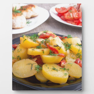 Stewed potatoes with bell pepper closeup plaque