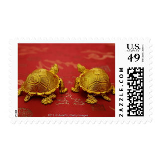 Still life of a pair of gold tortoise figurines stamps