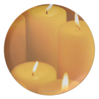 Still life of lighted candles party plates