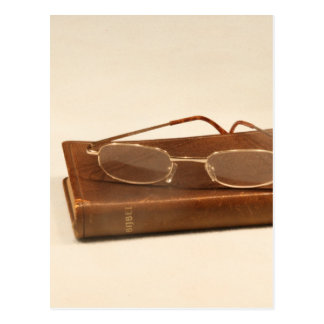 Still life with bible and reading glasses postcard