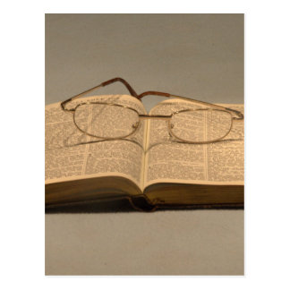 Still life with open bible and reading glasses postcard