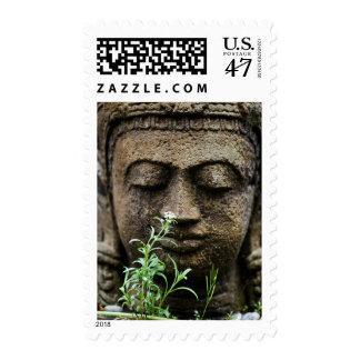Stone garden statue with flower postage