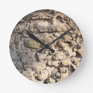 Stone wall of the large rough stones gray round clock