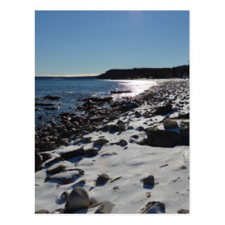 Stony cobble beach and blue waves in the snow postcard