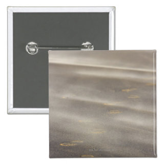 storm blowing shifting sand over boot prints 2 button