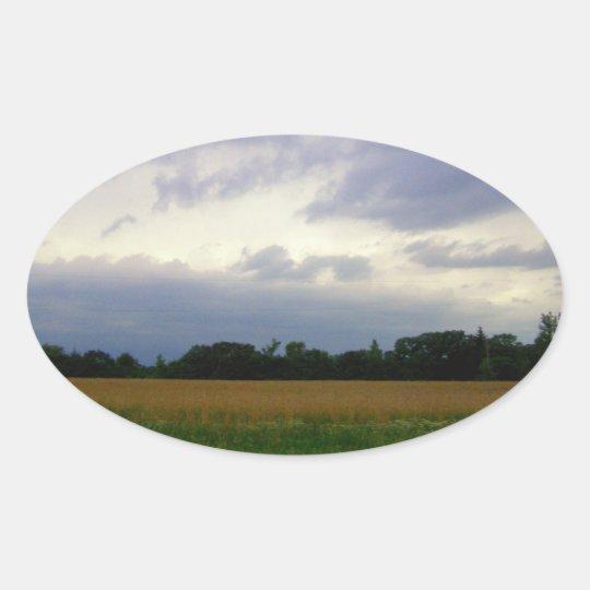 Stormy skies bad weather approaching farm fields oval sticker