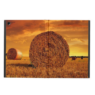 Straw bales on farmland with red cloudy sky cover for iPad air