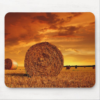Straw bales on farmland with red cloudy sky mouse pad