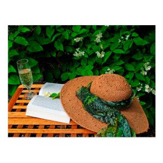 Straw hat, book and white wine in a summer garden postcard