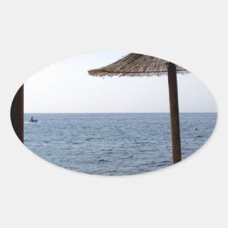 Straw Umbrellas on the Beach Oval Sticker