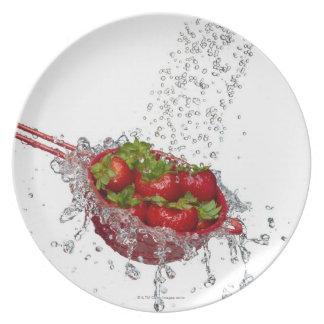 Strawberries in a red colander plates