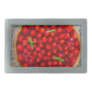 Strawberry cake with mint leaves on a rustic wood rectangular belt buckle