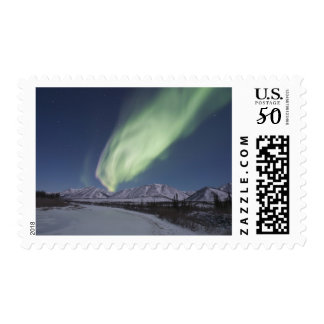 Streamers of aurora borealis fill the sky postage