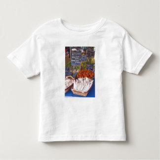 Street market merchant's stall with white toddler t-shirt