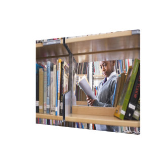 Student in school uniform looks at a book in a canvas print