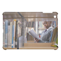 Student in school uniform looks at a book in a case for the iPad mini