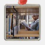 Student in school uniform looks at a book in a metal ornament