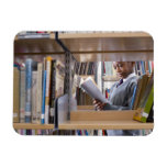 Student in school uniform looks at a book in a rectangular photo magnet